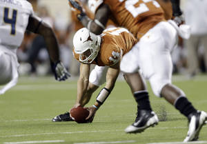 Photo -   Texas' David Ash (14) chases down a bobbled snap during the fourth quarter of an NCAA college football game against West Virginia, Saturday, Oct. 6, 2012, in Austin, Texas. West Virginia won 48-45. (AP Photo/Eric Gay)