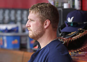 Photo - Milwaukee Brewers relief pitcher Will Smith sits in the dugout after they lost to the Cincinnati Reds 4-2 in a baseball game, Sunday, July 6, 2014, in Cincinnati. Smith was the losing pitcher, giving up a two-run home run to Jay Bruce in the eighth inning. (AP Photo/Al Behrman)