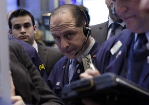 photo - In this Friday, Jan. 25, 2013, photo, Trader Michael Urkonis, center, works on the floor of the New York Stock Exchange. Wall Street appeared headed for a day of trade without drama Monday Jan. 28, 2013.  (AP Photo/Richard Drew)