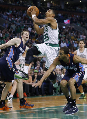 Photo - Boston Celtics' Phil Pressey (26) drives between Charlotte Bobcats' Cody Zeller (40) and Jannero Pargo (5) in the fourth quarter of an NBA basketball game in Boston, Friday, April 11, 2014. The Celtics won 106-103. (AP Photo/Michael Dwyer)