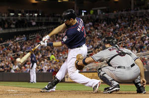 photo -   Minnesota Twins' Joe Mauer (7) hits an RBI single against Cleveland Indians relief pitcher Scott Maine as Indians catcher Lou Marson looks on during the seventh inning of a baseball game, Monday, Sept. 10, 2012, in Minneapolis. The Twins won 7-2. (AP Photo/Genevieve Ross)