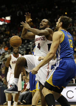 Photo - Atlanta Hawks power forward Paul Millsap (4) loses the ball as he drives against Golden State Warriors center Andrew Bogut (12) in the first half of an NBA basketball game on Friday, Jan. 3, 2014, in Atlanta. (AP Photo/John Bazemore)