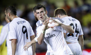 Photo - Real Madrid's Gareth Bale from Wales celebrates scoring against Villarreal during their La Liga soccer match at the Madrigal stadium in Villarreal, Spain, Saturday, Sept. 14, 2013. (AP Photo/Alberto Saiz)