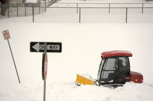 Photo - A Baltimore County worker clears snow from a walkway in Towson, Md. Thursday, Feb. 13, 2014. The storm was the biggest in Maryland in four years, prompting a state of emergency declaration by the governor. (AP Photo/Steve Ruark)