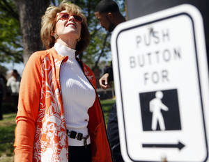 Photo - Ann Hargis, the first lady of Oklahoma State University, looks for a geocache hidden on campus. <cutline_credit_leadin>Photo by KT King, The Oklahoman</cutline_credit_leadin> <strong>KT King</strong>