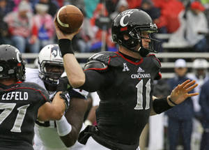 Photo - Cincinnati quarterback Brendon Kay (11) passes against Connecticut in the first half of an NCAA college football game, Saturday, Oct. 19, 2013, in Cincinnati. (AP Photo/Al Behrman)