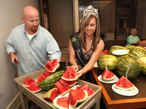 Photo - State Rep. Joe Dorman, D-Rush Springs, and 2012 Watermelon Queen May'zey Brown prepare Thursday to serve watermelon to workers and officials at the state Capitol. They were there to promote the annual Rush Springs Watermelon Festival that will be Aug. 11.  Photo BY JIM BECKEL, THE OKLAHOMAN