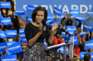 Photo -   First lady Michelle Obama gestures during a campaign rally for her husband, President Barack Obama, Friday, Nov. 2, 2102, at Virginia State University in Petersburg, Va. (AP Photo/Steve Helber)