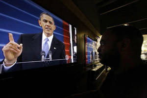 Photo - Richard Smith watches President Barack Obama deliver his inaugural address during the ceremonial swearing-in, on a television at a Best Buy department store in Springfield, Ill., Monday, Jan. 21, 2013. (AP Photo/Seth Perlman)