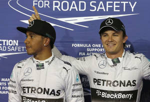 Photo - Mercedes drivers Nico Rosberg of Germany, who captured the pole position, right, second fastest time Mercedes driver Lewis Hamilton of Britain, left, pose for photographers after the qualifying session of the Bahrain Formula One Grand Prix at the Formula One Bahrain International Circuit in Sakhir, Bahrain, Saturday, April 5, 2014. (AP Photo/Hassan Ammar)