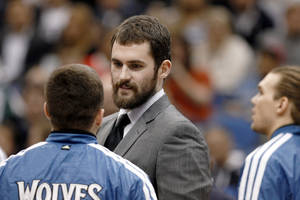 photo - Injured Minnesota Timberwolves forward Kevin Love talks to teammates during a timeout during the first half of an NBA basketball game against the San Antonio Spurs Wednesday, Feb. 6, 2013 in Minneapolis. (AP Photo/Genevieve Ross)