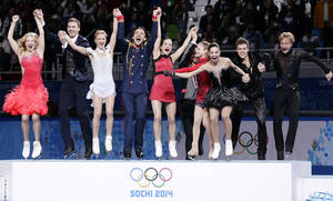 Photo - The Russian team jump onto the podium during the flower ceremony after placing first in the team figure skating competition at the Iceberg Skating Palace during the 2014 Winter Olympics, Sunday, Feb. 9, 2014, in Sochi, Russia. (AP Photo/Bernat Armangue)