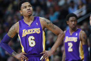 Photo - Los Angeles Lakers guard Kent Bazemore, front, looks on against the Denver Nuggets as guard MarShon Brooks, back, checks in to play in the first quarter of an NBA basketball game in Denver on Friday, March 7, 2014. (AP Photo/David Zalubowski)