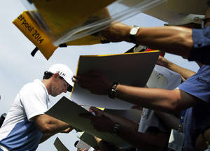 Photo - Rory McIlroy, of Northern Ireland, signs autographs after a practice round for the PGA Championship golf tournament at Valhalla Golf Club on Wednesday, Aug. 6, 2014, in Louisville, Ky. The tournament is set to begin on Thursday. (AP Photo/John Locher)