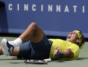 Photo - Rafael Nadal, from Spain, falls to the court after defeating John Isner 7-6 (8), 7-6 (3) to win the Western & Southern Open tennis tournament on Sunday, Aug. 18, 2013, in Mason, Ohio. (AP Photo/Al Behrman)