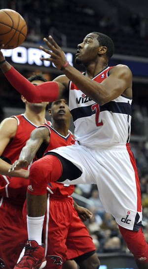 Photo - Washington Wizards guard John Wall (2) drives to the basket away from Atlanta Hawks guard Louis Williams during the first half of their NBA basketball game on Saturday, Jan. 12, 2013, in Washington. Wall had been sidelined since being diagnosed with a stress injury to his left kneecap in September. (AP Photo/Richard Lipski)