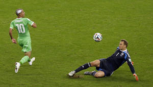 Photo - Germany's goalkeeper Manuel Neuer, right, clears a ball ahead of Algeria's Sofiane Feghouli during the World Cup round of 16 soccer match between Germany and Algeria at the Estadio Beira-Rio in Porto Alegre, Brazil, Monday, June 30, 2014. (AP Photo/Thanassis Stavrakis)
