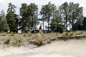 Photo - Retief Goosen, of South Africa, walks to the 18th green during a practice round for the U.S. Open golf tournament in Pinehurst, N.C., Monday, June 9, 2014. The tournament starts Thursday. (AP Photo/Chuck Burton)