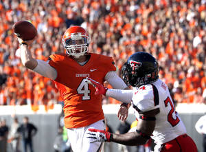 Photo - Oklahoma State's J.W. Walsh (4) throws a touchdown pass as Texas Tech's Bruce Jones (24) pressures him during a college football game between Oklahoma State University and the Texas Tech University (TTU) at Boone Pickens Stadium in Stillwater, Okla., Saturday, Nov. 17, 2012. Photo by Sarah Phipps, The Oklahoman
