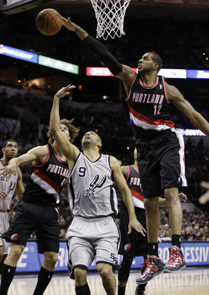 Photo - San Antonio Spurs' Tony Parker (9), of France, has his shot blocked by Portland Trail Blazers' LaMarcus Aldridge (12) during the first half on an NBA basketball game, Friday, Jan. 17, 2014, in San Antonio. (AP Photo/Eric Gay)