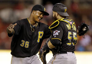 Photo - Pittsburgh Pirates starting pitcher Edinson Volquez, left, is congratulated by teammate Russell Martin after throwing a complete baseball game against the St. Louis Cardinals Thursday, July 10, 2014, in St. Louis. The Pirates won 9-1. (AP Photo/Jeff Roberson)