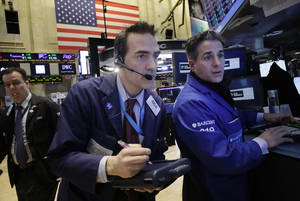 Photo - Gregory Rowe, center, places orders for stock with Anthony Rinaldi, right, at the New York Stock Exchange, Wednesday, Feb. 12, 2014. U.S. stocks are edging higher in early trading as the market extends its longest winning streak of the year. (AP Photo/Mark Lennihan)