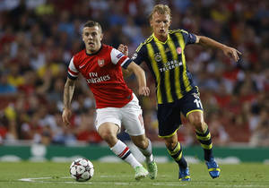 Photo - Arsenal's Jack Wilshere, left, competes with Fenerbahce's Dirk Kuyt during their Champions League qualifying play-off second leg soccer match at Emirates Stadium, London, Tuesday, Aug. 27, 2013. (AP Photo/Kirsty Wigglesworth)