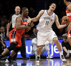 Washington Wizards' Kevin Seraphin, left, fouls Brooklyn Nets' Brook Lopez during the first half of the NBA basketball game Wednesday, Dec. 18, 2013, in New York. (AP Photo/Seth Wenig)