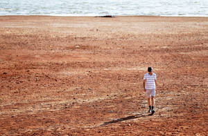 Photo - Paul Gilchrest, of Oklahoma City, walks across the receding shoreline of Lake Hefner recently. Oklahoma City has experienced record heat and drought this summer, similar to conditions in the city in the summer of 1936. PHOTO BY BRYAN TERRY, THE OKLAHOMAN