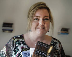 Photo - In the photo made Tuesday, Feb. 5, 2013, self publishing author Colleen Hoover posses and holds copies her books in Sulphur Springs, Texas. Hoover's romance novels books have made the New York Times bestseller list. (AP Photo/LM Otero)