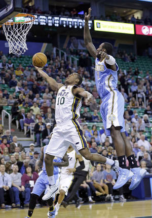 Photo - Utah Jazz's Alec Burks (10) goes to the basket as Denver Nuggets' J.J. Hickson (7) defends in the first quarter during an NBA basketball game Monday, Jan. 13, 2014, in Salt Lake City. (AP Photo/Rick Bowmer)