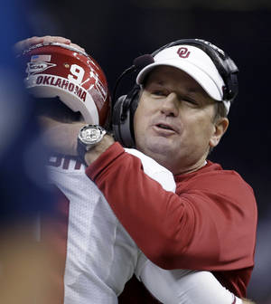 Photo - Oklahoma coach Bob Stoops hugs quarterback Trevor Knight during the first half of the Sugar Bowl NCAA college football game against Alabama, Thursday, Jan. 2, 2014, in New Orleans. (AP Photo/Rusty Costanza)