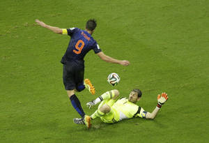 Photo - Netherlands' Robin van Persie dribbles Spain's goalkeeper Iker Casillas before scoring during the group B World Cup soccer match between Spain and the Netherlands at the Arena Ponte Nova in Salvador, Brazil, Friday, June 13, 2014.  (AP Photo/Christophe Ena)