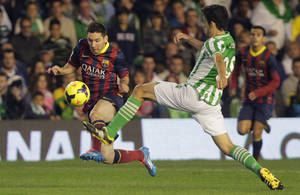Photo - Barcelona's Lionel Messi from Argentina, left, and Betis' Antonio Caro, right, fight for the ball during their La Liga soccer match at the Benito Villamarin stadium, in Seville, Spain, Sunday, Nov. 10, 2013. (AP Photo/Angel Fernandez)