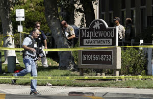 Photo -   A police official walks past the Maplewood Apartments after a shooting in Lakeside, Calif. Tuesday, Sept. 25, 2012. The San Diego County sheriff's Capt. Duncan Fraser said two deputies and a suspect have been shot while the deputies were trying to contact a child abuse suspect at the suburban apartment complex. (AP Photo/Gregory Bull)