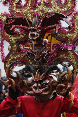 Photo - A man with a devil's mask dances in La Diablada in Pillaro, Ecuador, Monday, Jan. 6, 2014, to celebrate the end of the year and the start of the new one. The town of Pillaro kicks off the feast of La Diablada with neighborhoods competing to bring in as many people as possible dressed as different characters. Originally the devil costume was used to open up space to allow other participants to dance, but over the years the character gained popularity and became the soul of the feast. (AP Photo/Dolores Ochoa)