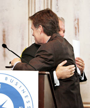 Photo - Oklahoma County District Attorney David Prater, left, hugs Wes Lane on Wednesday at the Oklahoma Business Ethics Consortium luncheon.  Photo by Paul B. Southerland, The Oklahoman