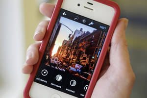 Photo - This Monday, June 9, 2014 photo shows the Instagram app, featuring new editing tools, on an iPhone posed for a photo in New York. Instagram, available for iOS 6.0 and later and Android phones, recently introduced 10 new editing tools. (AP Photo/Mark Lennihan)