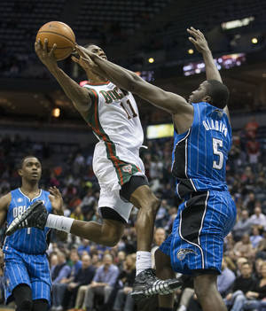 Photo - Milwaukee Bucks' Brandon Knight shoots over Orlando Magic's Victor Oladipo during the second half of an NBA basketball game Tuesday, Feb. 18, 2014, in Milwaukee. (AP Photo/Tom Lynn)