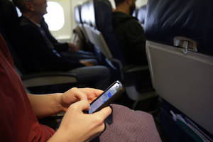 Photo - A passenger checks.3 her cell phone before a flight, Thursday, Oct. 31, 2013, in Boston. The Federal Aviation Administration issued new guidelines Thursday, Oct. 31, 2013, under which passengers will be able to use devices to read, work, play games, watch movies and listen to music, from the time they board to the time they leave the plane. (AP Photo/Matt Slocum)