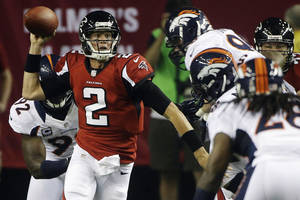 Photo -   Atlanta Falcons quarterback Matt Ryan (2) runs upfield as Denver Broncos free safety Quinton Carter (28) and defensive end Elvis Dumervil (92) defend during the first half of an NFL football game, Monday, Sept. 17, 2012, in Atlanta. (AP Photo/John Bazemore)