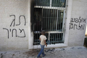 """Photo -   A Palestinian child stands outside a vandalized mosque in the West Bank town of Jabaa, near Ramallah, Tuesday, June 19, 2012. By July 1, the government has committed to destroying 30 apartments settlers built illegally on privately held Palestinian land. Acts of vandalism against Palestinian property have been expected ahead of that date because radical settlers routinely attack Palestinian targets in retaliation for government settlement policy they oppose. From left to right Hebrew writing reads, """"price tag"""" and """"Ulpana war."""" (AP Photo/Majdi Mohammed)"""