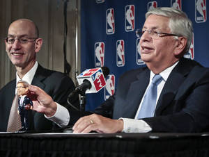 Photo - NBA Deputy Commissioner Adam Silver, left, smiles as NBA Commissioner David Stern shows a bobblehead doll in his likeness, during a press conference after a meeting of the NBA board of governors, Wednesday, Oct. 23, 2013 in New York.  Stern will formally step aside Feb. 1, 2014, after 30 years and Silver will become the new NBA commissioner.  (AP Photo/Bebeto Matthews)