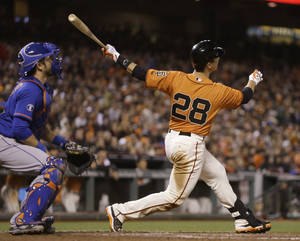 Photo - San Francisco Giants' Buster Posey follows through after hitting a two run home run off New York Mets' Carlos Torres in the eighth inning of a baseball game Friday, June 6, 2014, in San Francisco. (AP Photo/Ben Margot)