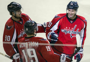 Photo - Washington Capitals right wing Troy Brouwer, right, is congratulated by center Marcus Johansson, left, and center Nicklas Backstrom after scoring a goal during the third period of an NHL hockey game on Sunday, March 16, 2014, in Washington. The Capitals won 4-2. (AP Photo/ Evan Vucci)