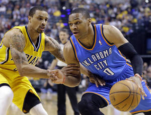 Photo - Oklahoma City Thunder guard Russell Westbrook, right, drives against Indiana Pacers guard George Hill in the second half of an NBA basketball game in Indianapolis, Sunday, April 13, 2014. (AP Photo/Michael Conroy)