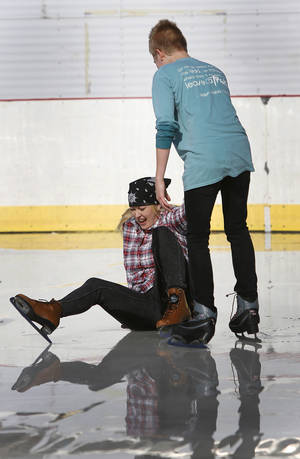 Photo - Austin Pruett helps his mother, Melissa Kissner, to her feet after she takes a spill Saturday at the outdoor ice rink at Marc Heitz Chevrolet. PHOTO BY JIM BECKEL, FOR THE OKLAHOMAN <strong>Jim Beckel</strong>