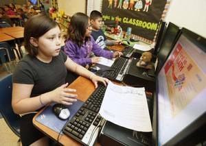 Photo - Hemileigh Flores (left), Karen Flores, and Alberto Martinez work on computers during the final day of school at Britton Elementary School. By Paul Hellstern, The Oklahoman <strong>PAUL HELLSTERN</strong>