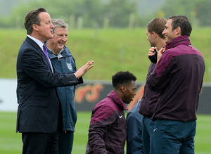 Photo - Britain's Prime Minister,  David Cameron, left, chats with England football manager Roy Hodgson, 2nd left, and players, Daniel Sturridge, centre, Steven Gerrard, 2nd right, and Frank Lampard during his visit to England's football training headquarters, St Georges Park, in Burton-Upon-Trent, central England, Thursday, May 29, 2014. (AP Photo/Andrew Yates, Pool)