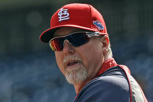 Photo -   FILE - In this Oct. 10, 2012, file photo, St. Louis Cardinals hitting coach Mark McGwire watches batting practice before Game 3 of the National League division baseball series against the Washington Nationals in Washington. McGwire was hired Wednesday, Nov. 7, as hitting coach for the Los Angeles Dodgers, where he will work with All-Star sluggers Matt Kemp and Andre Ethier. (AP Photo/Pablo Martinez Monsivais, File)